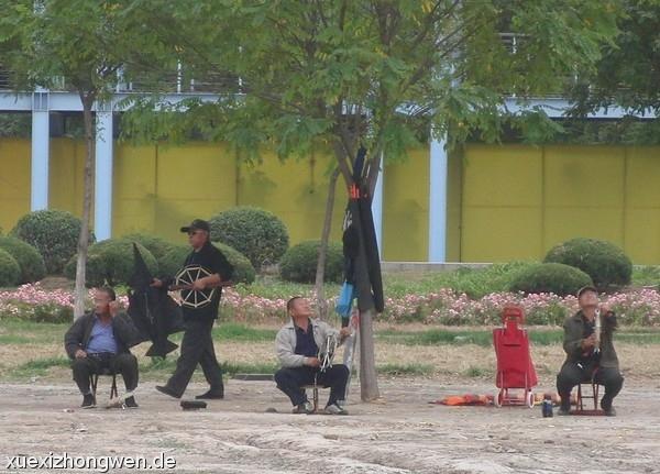 Chinesische Männer bei ihrem Hobby Drachen steigen lassen